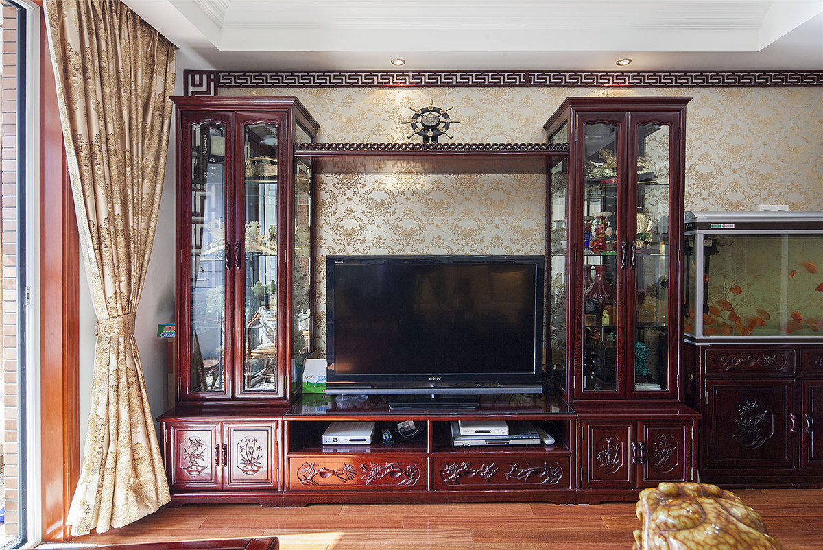 电视背景墙由传统的红木家具配上金色的墙纸